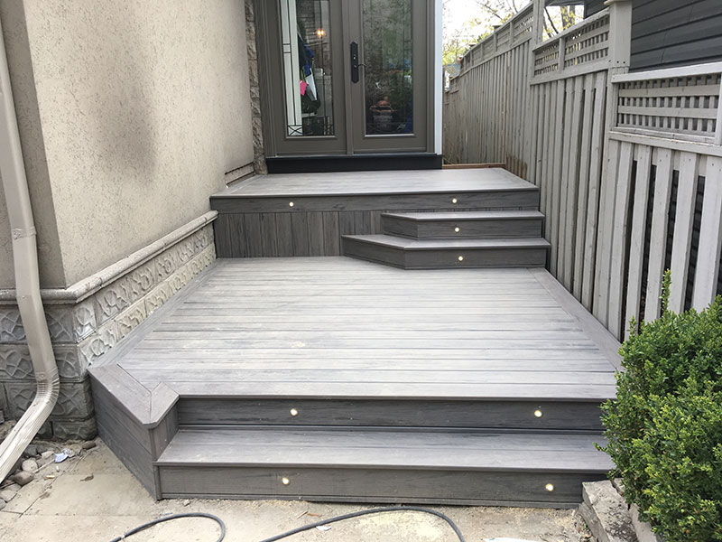 New wooden deck in front with handrails