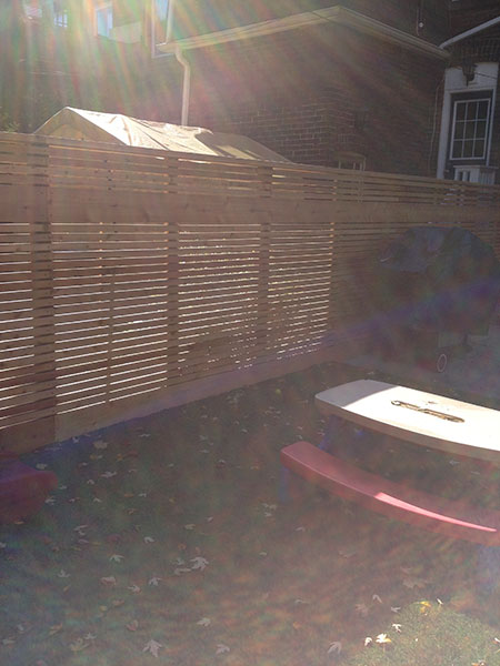 Wooden fences in backyard with bbq and table