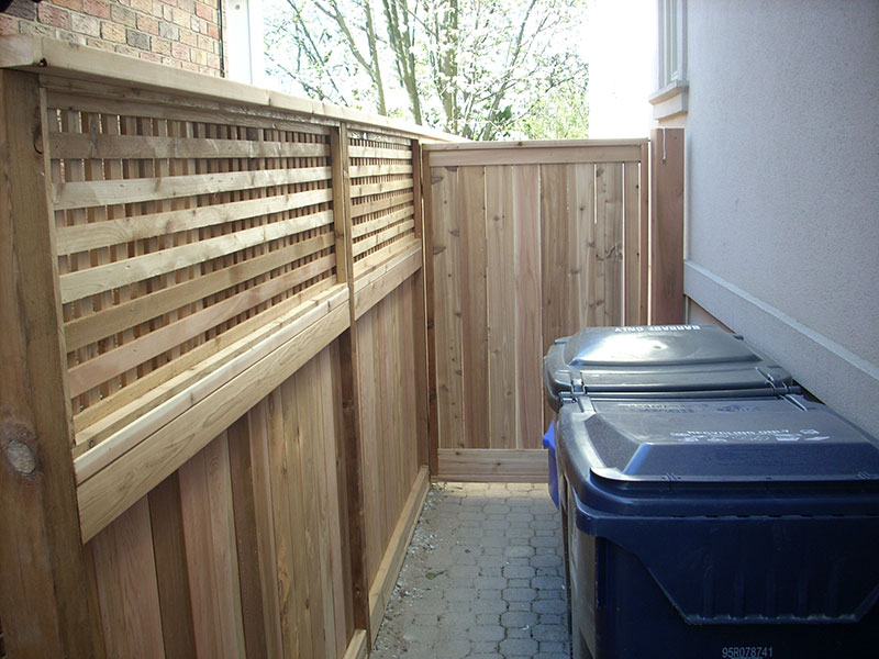 New wooden fences near garbage bins